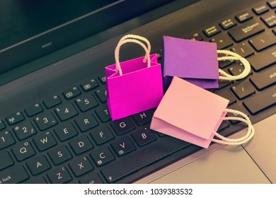 Online shopping concept, Three colorful paper shopping bags on notebook keyboard. E-commerce is the purchase of products and services on the internet can purchase goods or services foreign country.