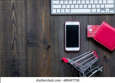 Online shopping concept. Shopping trolley near bank card, keyboard, phone on dark wooden background top view copyspace