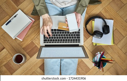 Online shopping concept. Unrecognizable woman sitting at floor, drinking tea and looking at laptop, pay for purchases by credit card