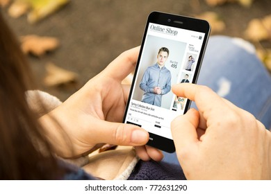 online shopping concept: woman holding a 3d generated smartphone with online shop on the screen. Graphics on screen are made up.