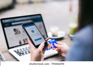 Online shopping concept, young asian woman with payment success on mobile phone screen using credit card to buy product on online retail shop with laptop computer at coffee cafe, lifestyles technology