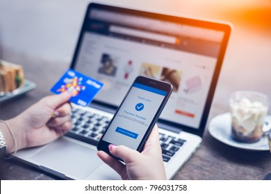 Online shopping concept, young woman hands holding mobile smart phone showing payment success on screen and credit card with laptop on table while sitting in coffee shop, lifestyles technology