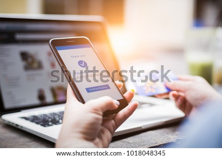 Online shopping concept, young woman hands holding mobile phone showing payment success information on screen with credit card and laptop computer on table while relax at home