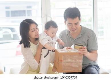 Online shopping with credit card. Happy Asian family at home, natural living lifestyle indoors.