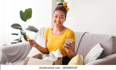 Online Shopping And Delivery Service Concept. Happy black woman holding credit card and cellphone, received package, unpacking cardboard box with white sneakers, sitting on the sofa in living room