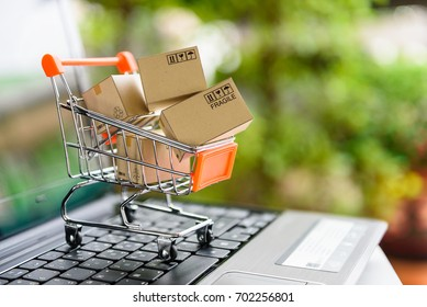 Online shopping and delivery service concept. Paper boxes in a shopping cart on a laptop keyboard, this image implies online shopping that customer order things from retailer sites via the internet.
