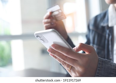 Online shopping, digital banking, E-commerce concept. Woman hand using mobile smart phone, tablet payments and holding credit card online shopping with laptop computer on table