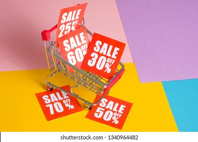 Online shopping discount concept. Red labels with percents in trolley on a multicolored background.