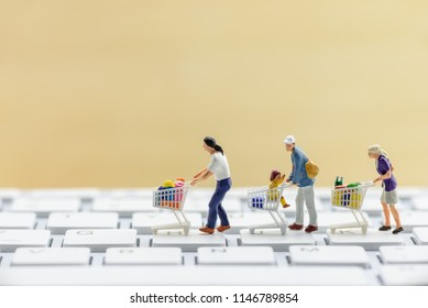 Online shopping / ecommerce concept : Miniature figurine shopper push a shopping cart on a computer keyboard, depicts buyers or consumers order or buy things from retailer stores over the internet