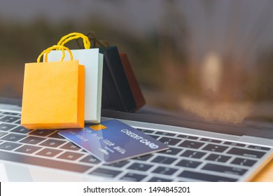 Online shopping and e-commerce concept. Paper shopping bags and mock-up of credit card on laptop keyboard with nature background on screen. Consumer buy products directly anywhere anytime from seller.
