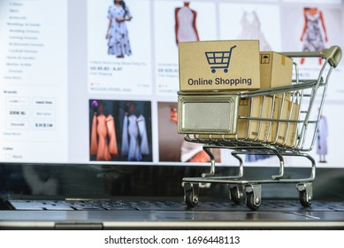 Online shopping / e-commerce and customer experience concept : Shopping cart with boxes on a computer, depicts consumers / buyers buy or purchase goods and service from home during quarantine period