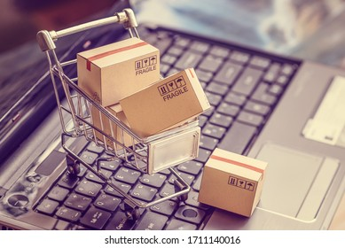 Online shopping  e-commerce and customer experience concept : Boxes with shopping cart on a laptop computer keyboard, depicts consumers  buyers buy or purchase goods and service from home or office