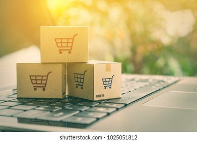 Online shopping / ecommerce and delivery service concept : Paper cartons with a shopping cart or trolley logo on a laptop keyboard, depicts customers order things from retailer sites via the internet.