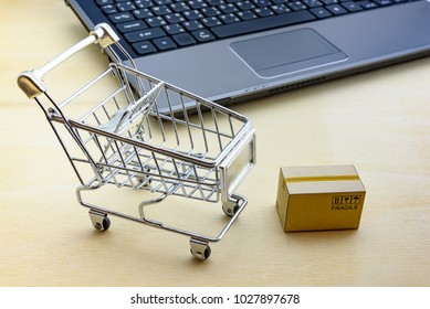 Online shopping / ecommerce and delivery service concept : Paper cartons with a shopping cart or trolley near a laptop keyboard, depicts customers order things from retailer sites via the internet.