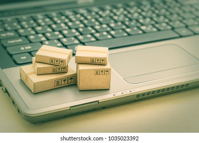 Online shopping / ecommerce and delivery service concept : Paper cartons on a laptop, depicts trendy customers always order personal goods or things from retailer sites over the internet from home.