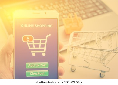 Online shopping / ecommerce and delivery service concept : White smart device runs an online shopping app with 5 items in a cart, depicts customers order things from retailer sites over the internet.