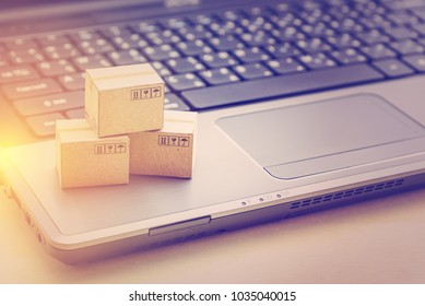 Online shopping / ecommerce and delivery service concept : Paper cartons or boxes on a laptop keyboard, depicts modern or trendy customers always order things from retailer sites over the internet.
