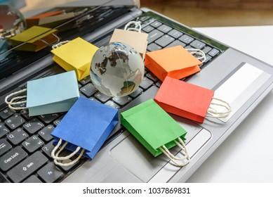 Online shopping / ecommerce and delivery service concept : Color paper shopping bags on a laptop keyboard, depicts trendy customers always order things from retailer sites over the internet worldwide.