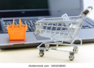Online shopping / ecommerce and delivery service concept : Shopping basket and a shopping cart or trolley near a laptop computer, depicts customers order things from retailer sites over the internet.