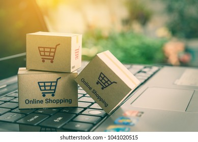 Online shopping / ecommerce and delivery service concept : Paper boxes with shopping cart symbol on a laptop keyboard, depicts trendy customers always order things from retailer sites over internet.