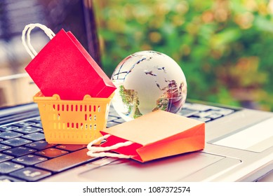 Online shopping / ecommerce and delivery service concept : Shopping bags, world globe, small shopping basket on a laptop keyboard, depicts customers order things from retailer sites via the internet.