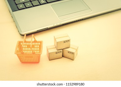 Online shopping / ecommerce and delivery service concept : Cartons or boxes, supermarket basket, a laptop, depicts modern or trendy customers always order things from retailer sites over the internet.