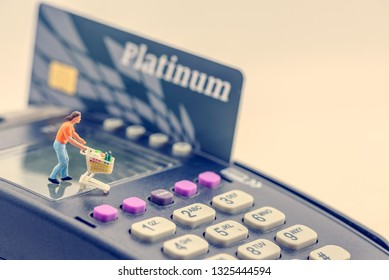 Online shopping / e-commerce and delivery service concept : Miniature figurine consumer shopper pushes a shopping cart on a credit card swipe machine or smart card reader, electronic payment terminal