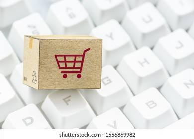 Online shopping, e-commerce shopping experience concept : Box / carton with shopping cart or a trolley on computer keyboard, depicts consumer / customer / buyer buy goods and service direct from home