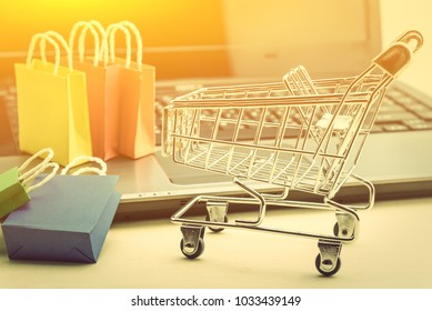Online shopping and ecommerce over internet concept : 5 shopping bags and a silver shopping cart with a laptop computer, depicts consumers always buy goods or things directly from online retail store.