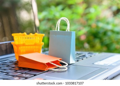 Online shopping and ecommerce over internet concept : Paper shopping bags, shopping baskets on a laptop computer, depicts consumers always buy gadget, goods or things directly from online retail store