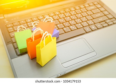 Online shopping and ecommerce over internet concept : Paper shopping bags on a laptop computer, depicts modern lifestyle consumers always buy personal goods or things directly from online retail store