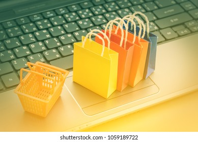 Online shopping and ecommerce over internet concept : Shopping bags and a plastic shopping basket on a laptop computer, depicts consumers always buy goods or things directly from online retail store.