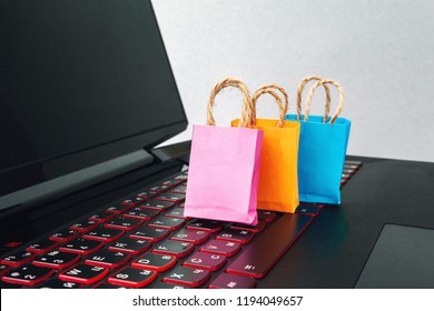 online shopping / e-commerce sale and delivery service concept, discounts, black Friday, sale: shopping cart multicolored packages and boxes with trolleybus logo on laptop keyboard