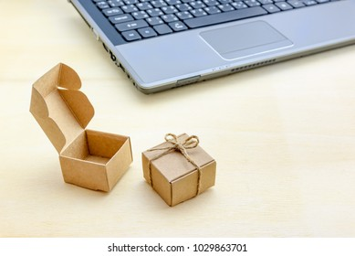 Online shopping and ecommerce via internet concept : Present / paper gift box (opened and closed) near laptop, depicts consumer always buys and sends goods or things directly from online retail stores