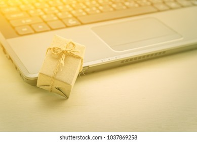 Online shopping and ecommerce via internet concept : Wrapped present / paper gift box with bow near a laptop, depicts consumer always buys and sends goods or things directly from online retail stores.