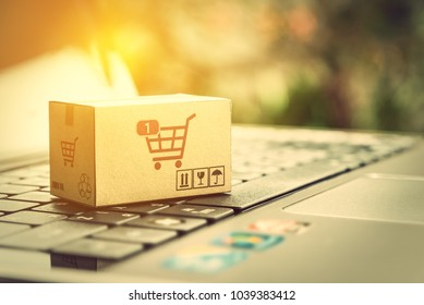 Online shopping and ecommerce via internet concept : One paper box with shopping cart logo on a laptop computer, depicts consumer always buys personal goods or things directly from online retail store