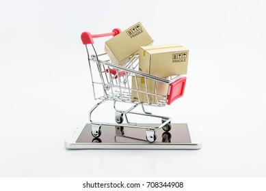 Online shopping and ecommerce via internet concept : Boxes in a shopping cart or metal trolley on a white mobile smartphone . Consumer always buy or shop goods and things from online retail stores .
