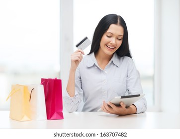online shopping, electronics and gadget concept - smiling woman with blank screen tablet pc and shopping bags