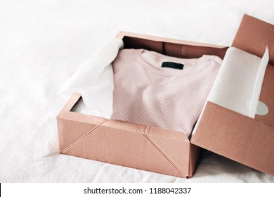 Online shopping fashion items opening box on a white background with copy space