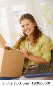 Online shopping. Happy young woman sitting on sofa at home, opening a cardboard box checking items she ordered online.