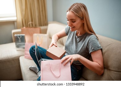 Online shopping at home. Young excited woman is unboxing her parcel, ordered by internet, while sitting on the sofa
