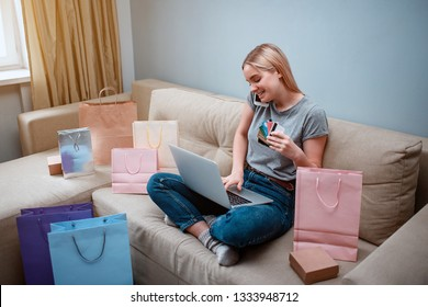 Online shopping at home. Young smiling shopper with laptop and credit cards is ordering by smarthphone in online shop while sitting on a sofa with shopping bags