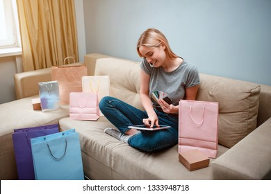 Online shopping at home. Young smiling shopper with tablet and credit cards is ordering by smarthphone in online shop while sitting on a sofa with shopping bags
