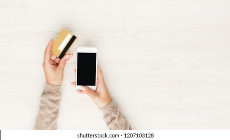 Online shopping in internet concept. Woman using credit card and blank smartphone, white wooden table background, top view