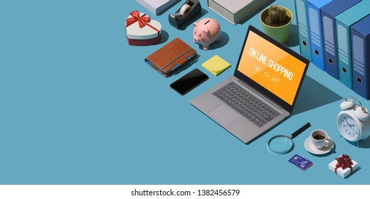 Online shopping: isometric laptop, credit cards and office items on a desktop, blank copy space