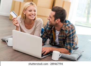Online shopping makes life easier. Smiling young couple laying on the floor of their new apartment and shopping through Internet while cardboard boxes laying in the background