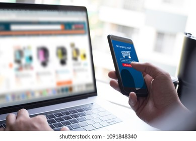 Online shopping. Man, customer using mobile smartphone purchasing products from website and mobile banking, searching items on webpage laptop computer. E commerce concept