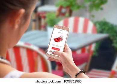 Online shopping with mobile phone. Red shoes on store web site. Woman use smart phone in coffee shop or restaurant.