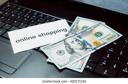 Online shopping. Money on the laptop keyboard.