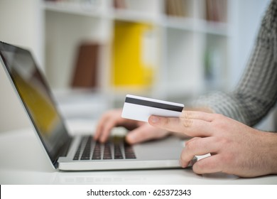 Online shopping in office using laptop and credit card, cropped photo